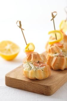 Profiteroles au fromage à pâte molle, poisson rouge et herbes. un repas gastronomique pour la table des fêtes.
