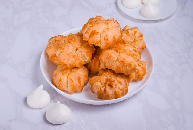 Profiteroles dessert à la crème sur une assiette blanche