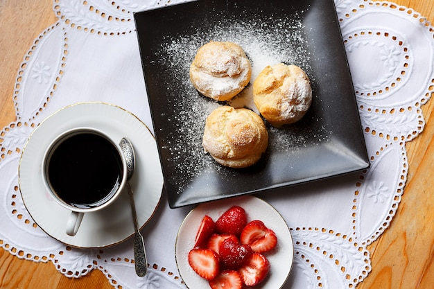 Profiteroles maison sur assiette foncée, fraise, broderie blanche