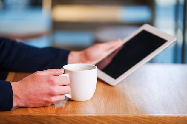 Profitez des avantages du wi-fi gratuit. gros plan d'un homme tenant une tablette numérique tout en dégustant un café au café