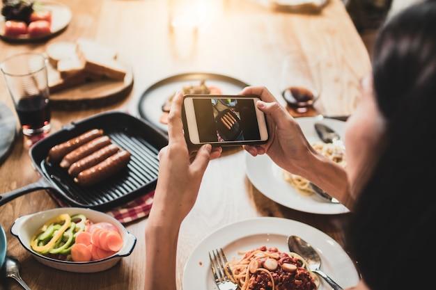 Profitez de dîner en train de manger fête et fête avec des amis et prendre des photos par téléphone