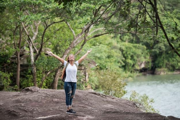 Profitez de la jeune femme heureuse avec sac à dos en levant la main avec la nature.