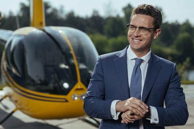 Profitez de voler. bel homme d'affaires optimiste dans un costume souriant joyeusement en attendant un tour en hélicoptère et en vérifiant sa montre