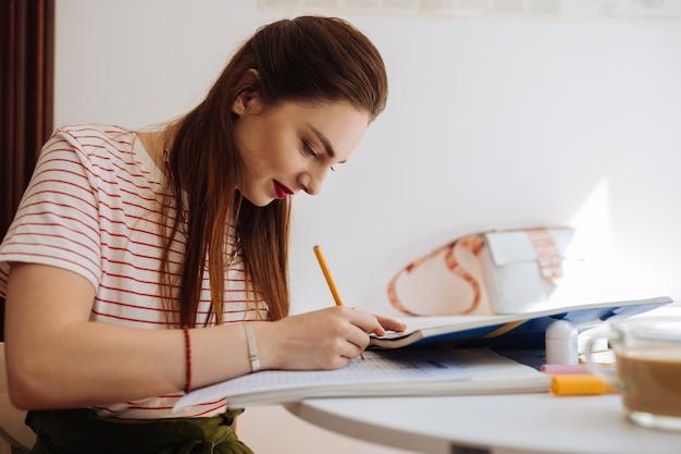 Profitez de votre étude. étudiante mignonne gardant le sourire sur son visage tout en complétant le test
