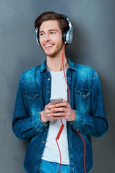 Profitez de votre piste préférée! beau jeune homme au casque tenant un téléphone portable