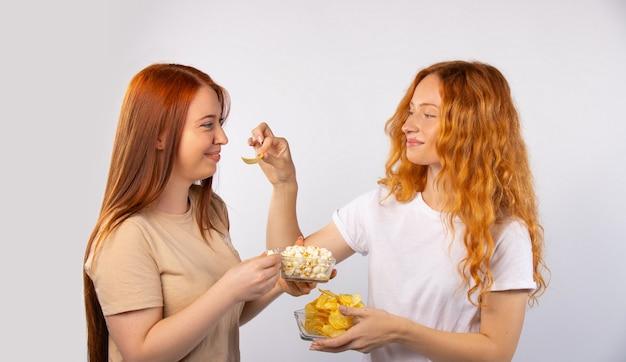 Profitez de votre temps. les copines aux cheveux roux mangent des chips et du pop-corn, rient et se détendent. photo sur un mur blanc.
