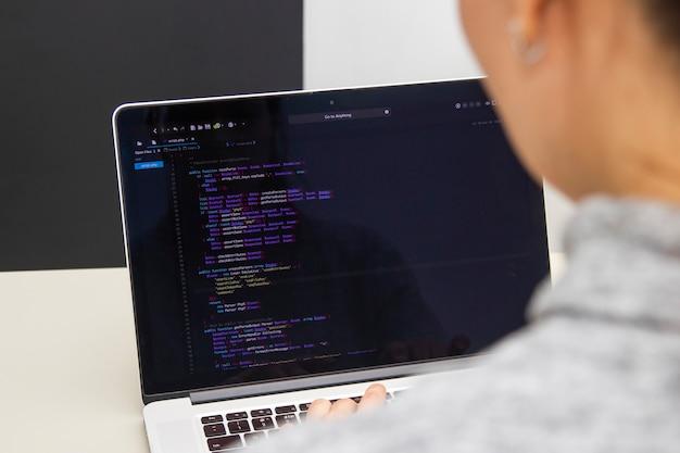 Un programmeur codant sur un ordinateur portable sur le lieu de travail