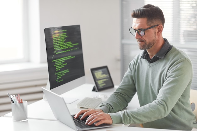 Programmeur informatique mature programmation et codage de nouvelles technologies tout en tapant sur un ordinateur portable à la table au bureau