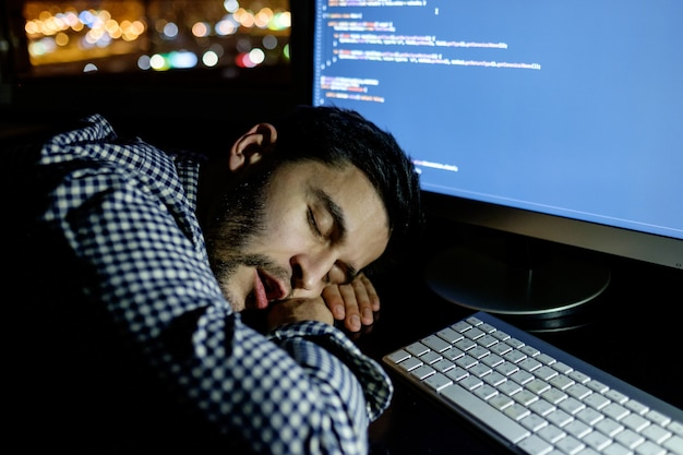 Programmeur pigiste tombant face cachée en faisant une sieste