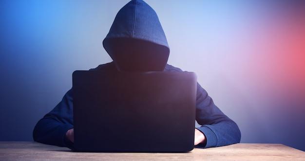 Programmeur ou pirate informatique en tapant le code sur le clavier de l'ordinateur portable