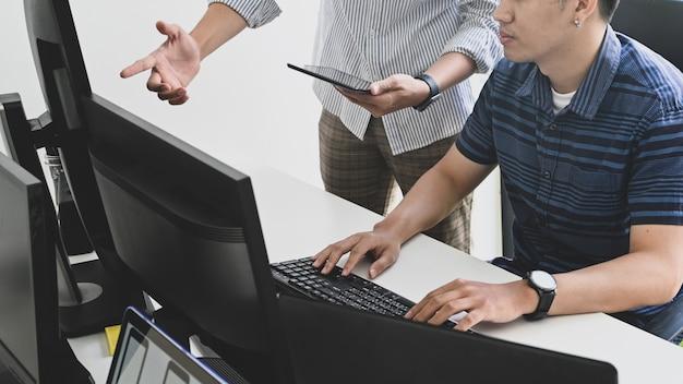 Programmeur de plans rognés consultant une tablette et un ordinateur sur l'espace de travail du développeur.