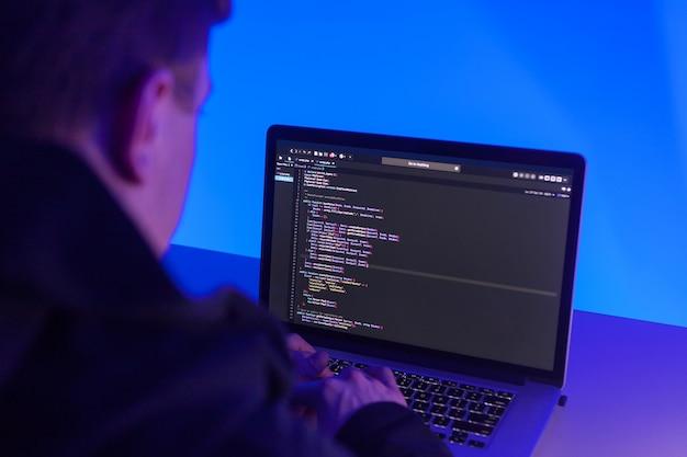 Programmeur travaillant sur ordinateur portable dans son studio