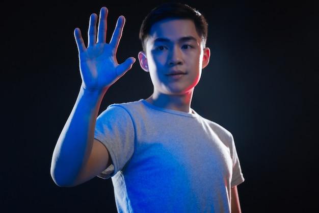Progrès technologique. homme asiatique sérieux à l'aide de la technologie moderne en se tenant debout sur fond noir