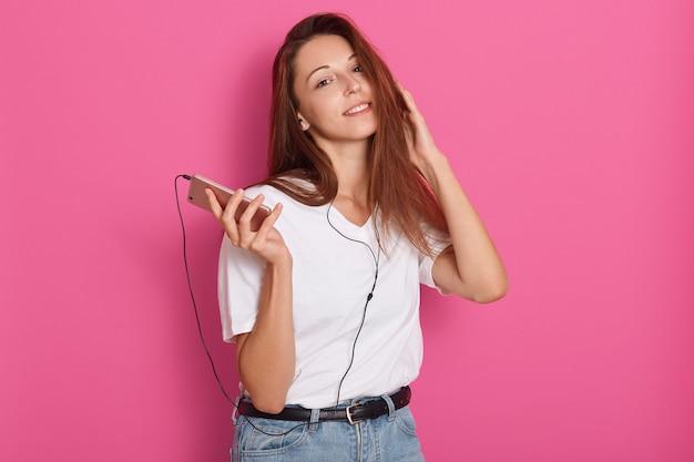Projectile studio, de, jeune femme, écouter musique, à, écouteurs, tenue, smartphone, dans, mains, regarder appareil-photo, délassant, chez soi