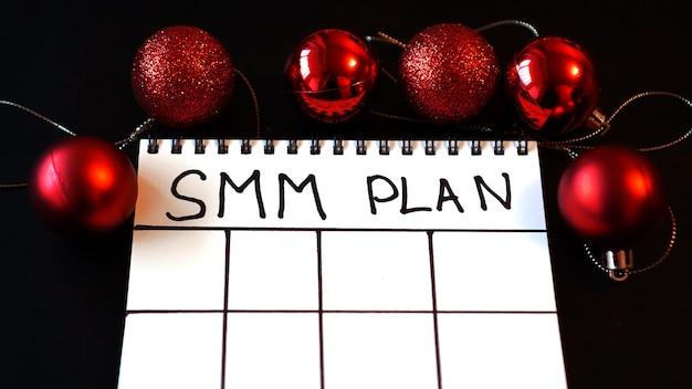 Projet indépendant. plan smm vierge. feuille blanche sur un fond festif noir avec des boules de noël rouges