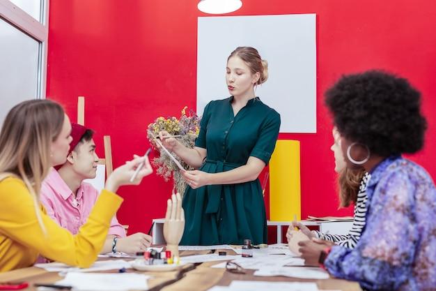 Projet de présentation. élève diligent aux cheveux blonds de l'école d'art portant une robe verte présentant le projet
