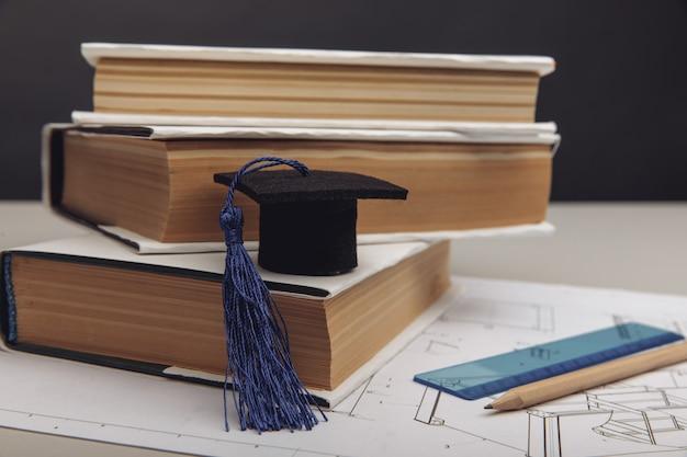 Projet technique et casquette de remise des diplômes avec concept de formation en ingénierie de livres