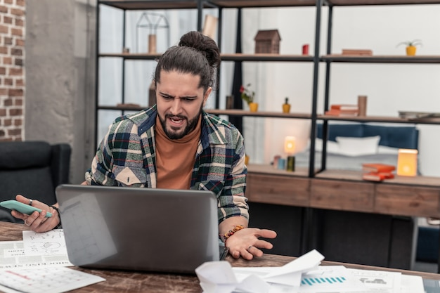 Des projets difficiles. jeune homme malheureux regardant l'écran de l'ordinateur portable tout en ayant des problèmes avec son travail
