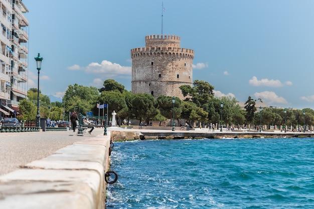 Une promenade en bord de mer à thessalonique avec une tour blanche du patrimoine byzantin derrière des arbres