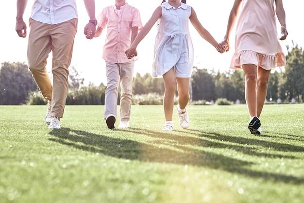 Promenade en famille famille de quatre personnes marchant sur les jambes des champs herbeux closeu
