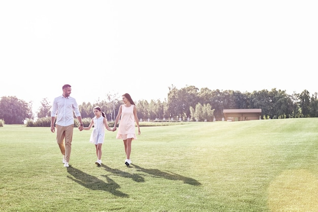 Promenade en famille famille de trois personnes marchant sur un terrain herbeux souriant hap