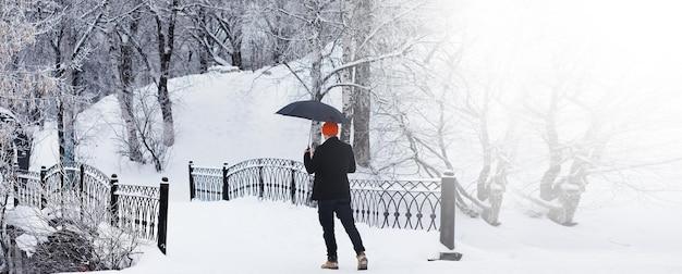 Promenade d'hiver avec un parapluie. homme dans un manteau avec un parapluie, marche dans le contexte du paysage d'hiver, vue d'hiver