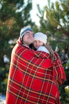 Promenade hivernale à travers les bois. le gars dans la couverture à carreaux rouge enveloppe la fille pour qu'elle se réchauffe