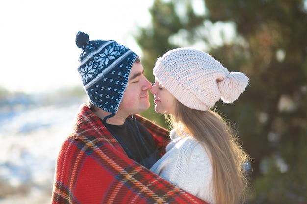 Promenade hivernale à travers les bois, le mec avec la fille embrassée, enveloppé dans un plaid à carreaux rouges