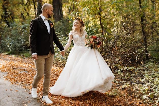 Promenade des mariés à travers la forêt d'automne