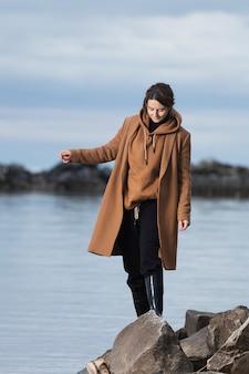 Une promenade romantique d'une femme aux cheveux bouclés en manteau de laine beige posant sur la pierre en mer