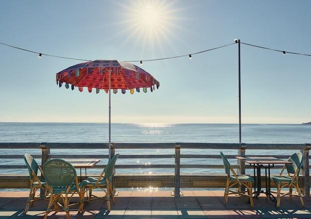 Promenade avec tables et chaises avec vue sur la mer