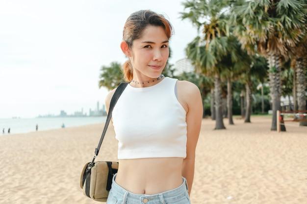 Promenade touristique de femme sur la plage avec des palmiers en arrière-plan