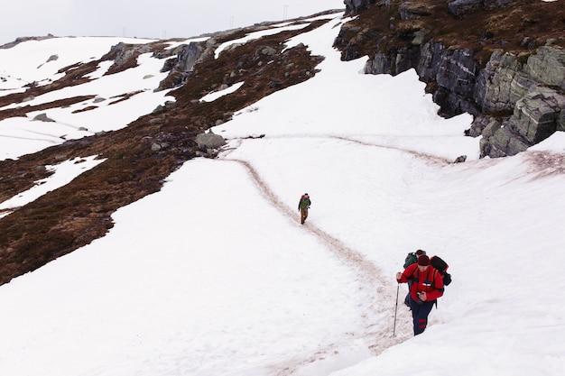 Promenade touristique à travers la neige dans les montagnes