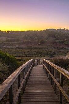 Promenade à travers les dunes à l'aube avec des montagnes en arrière-plan