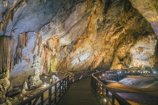 Promenade à travers la grotte éclairée du paradis au vietnam