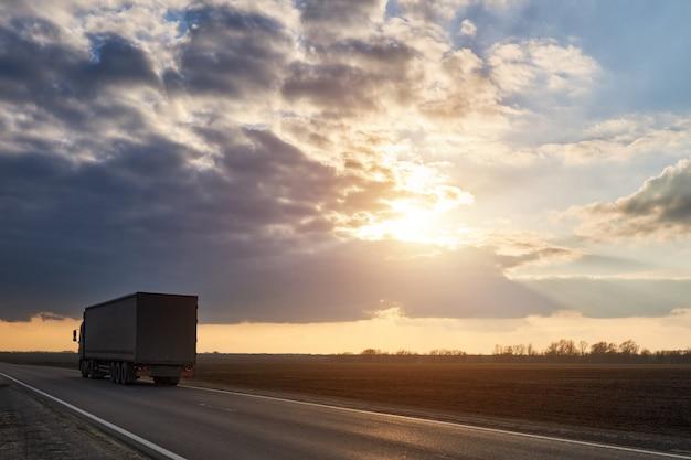 Promenades en camion sur l'autoroute dans le contexte de beaux nuages au coucher du soleil