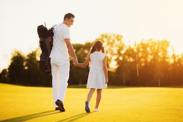 Promenades en famille par parcours transportant l'équipement de golf.