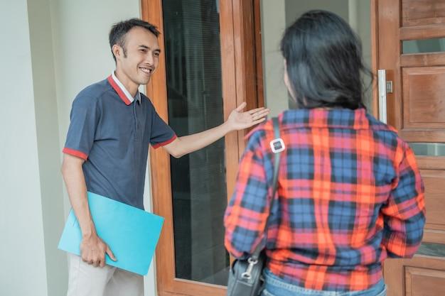 Promoteur immobilier masculin avec un geste de la main lors de l'invitation des clients à entrer dans la porte