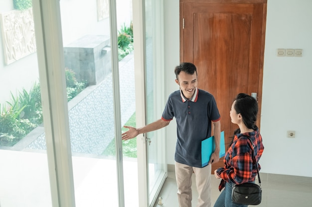 Le promoteur immobilier masculin se tient près de la porte vitrée avec un geste de la main pour inviter la femme à jeter un œil à l'arrière-cour de la nouvelle maison