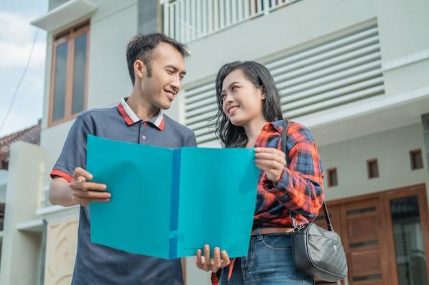 Les promoteurs immobiliers masculins montrent des certificats de maison aux clients possédant de nouvelles maisons