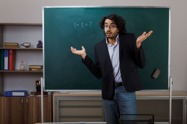 Propagation confuse des mains jeune enseignant portant des lunettes debout devant le tableau noir en classe