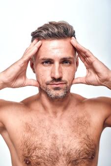 Proportions parfaites homme beau et sexy avec un chaume tenant la tête dans les mains et regardant