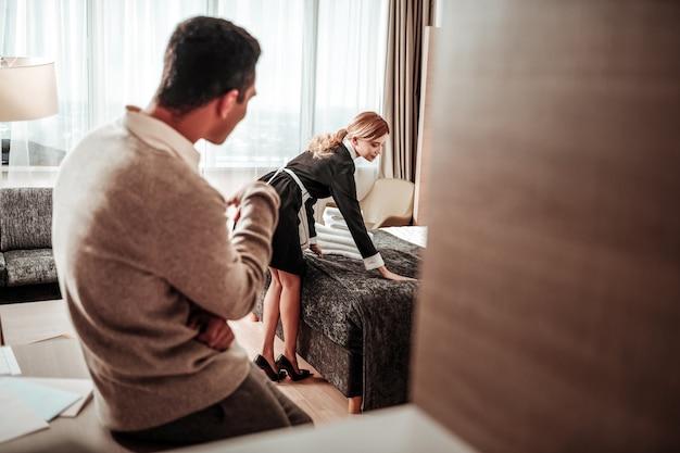 À propos du harcèlement. l'homme pense au harcèlement sexuel en regardant sa jeune femme mince travaillant