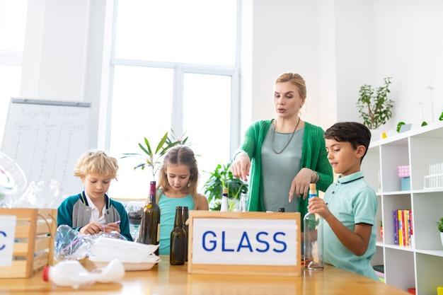 À propos du recyclage du verre. une enseignante du primaire parle à ses élèves du recyclage du verre et du tri des déchets