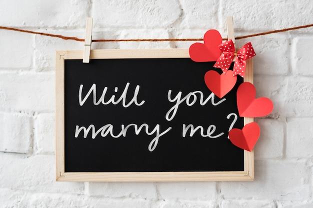 Proposition de mariage écrite sur un tableau noir
