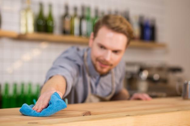 Propreté absolue. mise au point sélective d'un plumeau bleu utilisé pour nettoyer la surface de la table