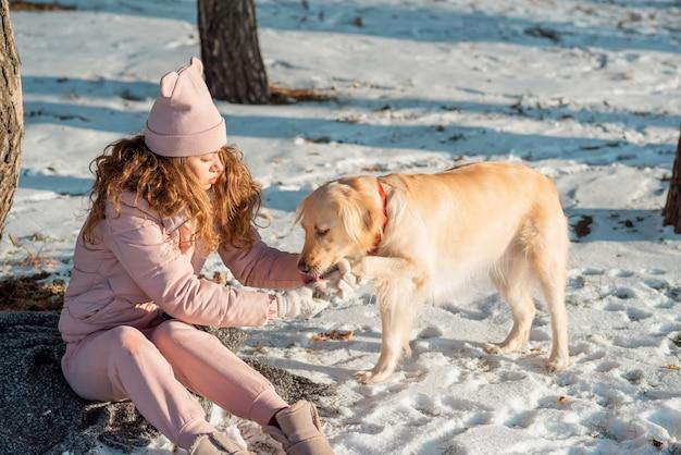 Le propriétaire aide son adorable chien golden retriever à nettoyer les pattes. les pattes du chien gèlent en hiver et la neige est bouchée.