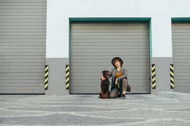 Propriétaire et animal assis sur rue contre mur gris