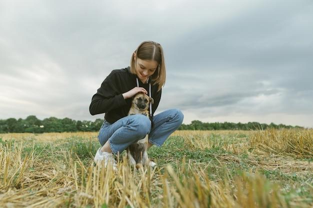 Propriétaire de belle fille et petit chien sur un champ biseauté