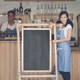 Propriétaire de café femme asiatique avec tableau blanc